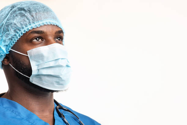 Junger schwarzer Chirurg, der sich den Kopierraum anschaut – Foto
