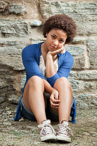 Young Black Teenage Girl in Blue Sitting by Stone Wall stock photo