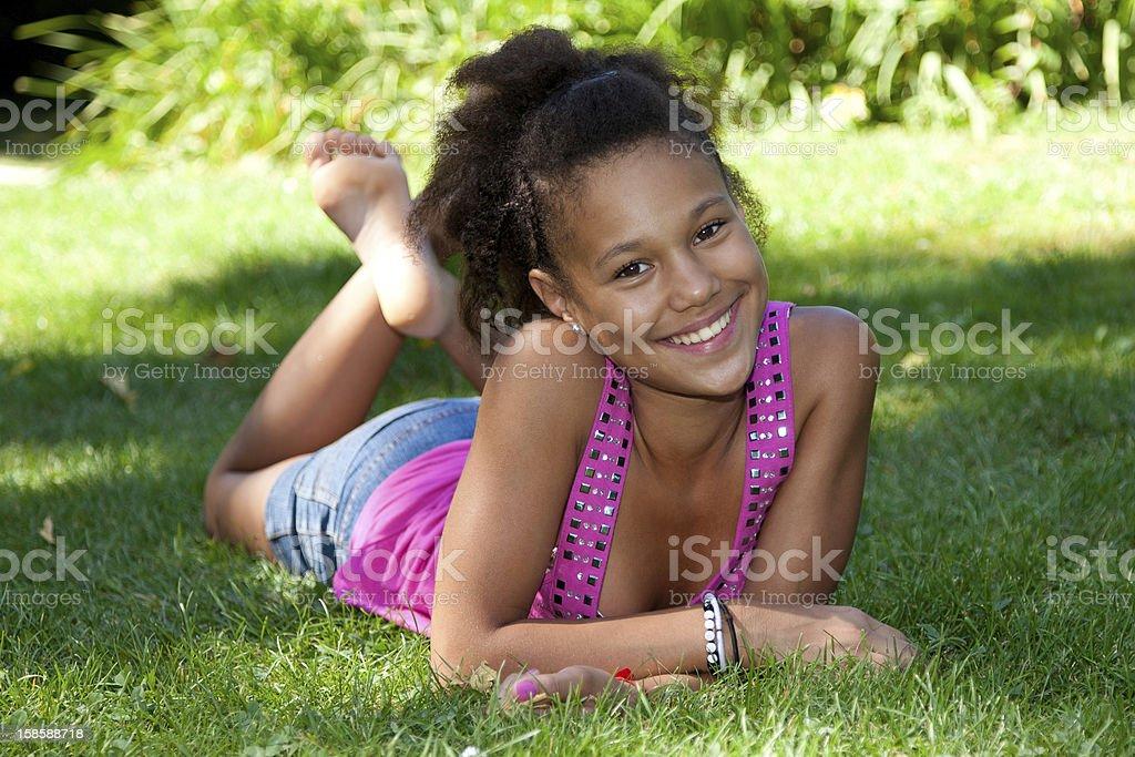 Young black teenage girl lying on the grass — Stock Photo