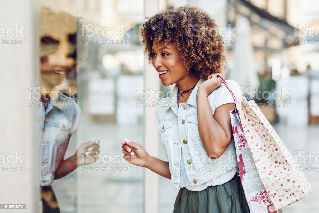 Young black woman, afro hairstyle, looking at a shop window stock photo