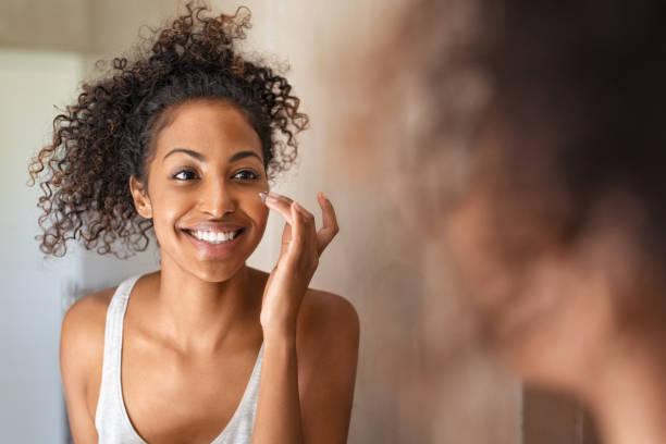 Junge schwarze Frau, die Hautcreme auftragen – Foto