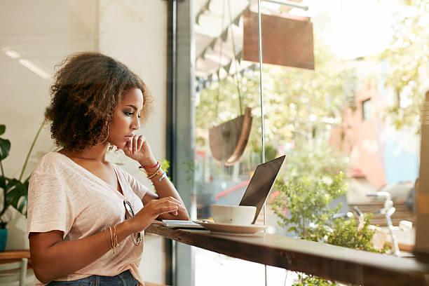 junge schwarze frau mit laptop im café - coffee shop stock-fotos und bilder