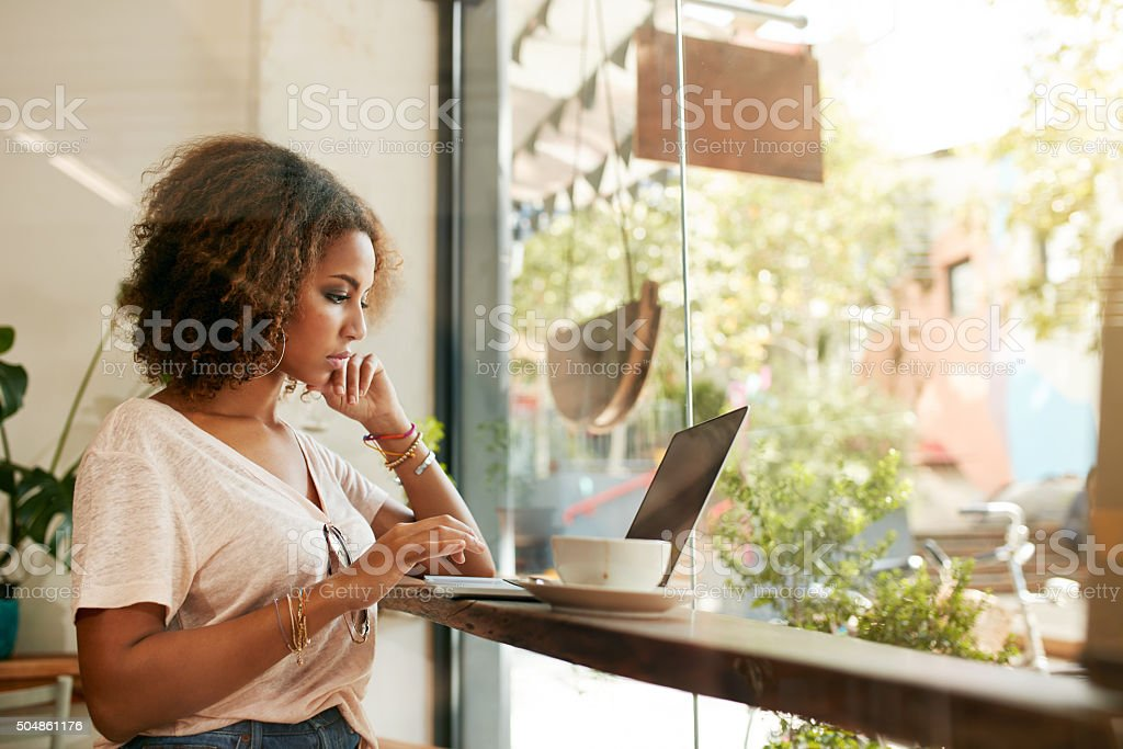 Young black woman at cafe using laptop stock photo