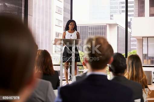 862718922 istock photo Young black woman at lectern presenting seminar to audience 639467978