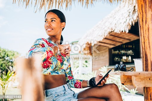 Millennial Black woman  summer resort. She is enjoying her  summer vacation in Caribbean.