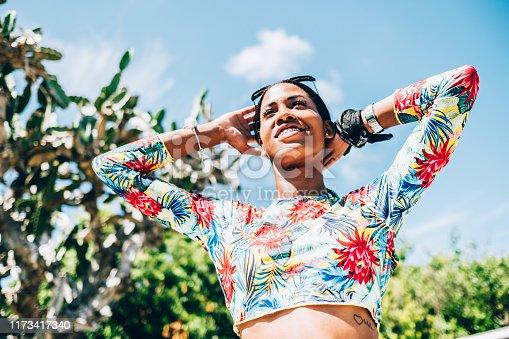 Millennial Black woman at  summer resort garden. She is enjoying her  summer vacation in Caribbean.