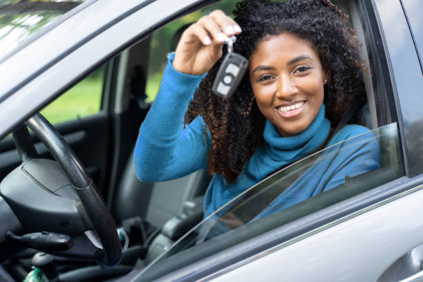 Young black woman at the wheel showing car key stock photo