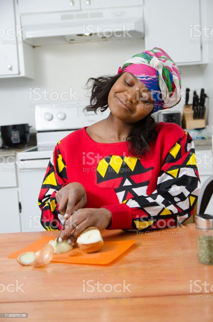 Junge schwarze Frau, die eine Zwiebel schneiden – Foto