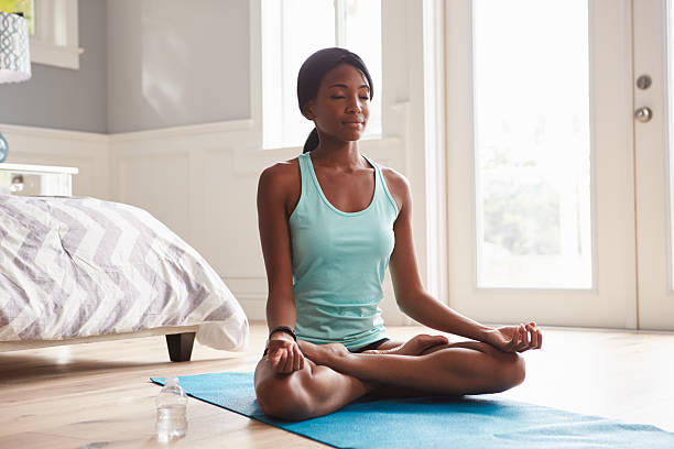 Young black woman doing yoga at home in the lotus Young black woman doing yoga at home in the lotus position lotus position stock pictures, royalty-free photos & images