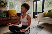 istock Young black woman doing yoga at home in the lotus position 1272749383