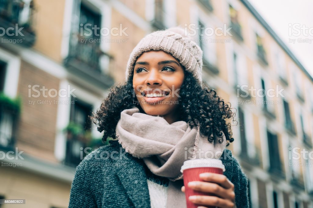 Young black woman drinking coffee wandering in the streets of Madrid on winter stock photo