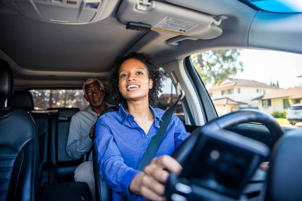 Young Black Woman Driving Car for Rideshare A young black woman drives a passenger in her car as a professional driver. passenger stock pictures, royalty-free photos & images
