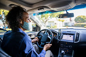 istock Young Black Woman Driving Car for Rideshare Wearing a Mask 1264854286