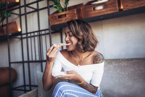junge schwarze frau in café pizza essen - essen tattoos stock-fotos und bilder