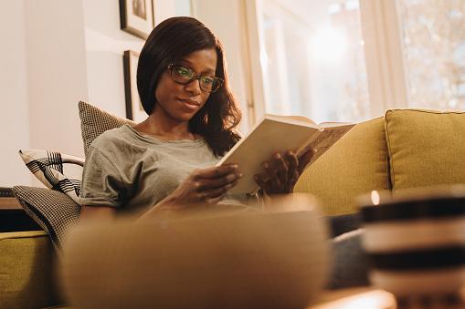 Jonge Zwarte Vrouw Genieten In Ontspannen Dag Thuis En Het Lezen Van Een Boek Stockfoto en meer beelden van Afrikaanse etniciteit