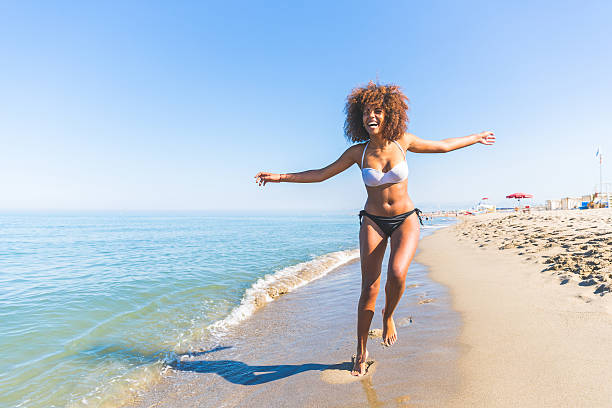 Young black woman having fun at seaside Young black woman having fun at seaside. She is twenty years old, mixed race caucasian and african black, with curly and voluminous hair, running with open arms and happy face. bikini stock pictures, royalty-free photos & images