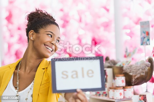 istock Young black woman holding SALE sign 468120082