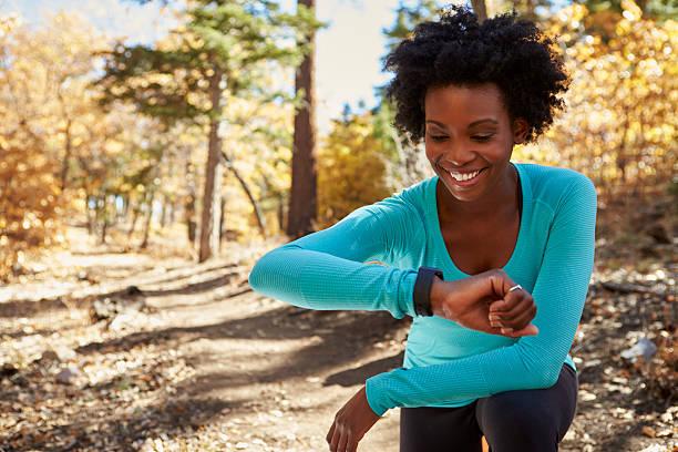 giovane donna in una foresta nera controlla smartwatch e sorridente - attrezzatura per esercizi foto e immagini stock