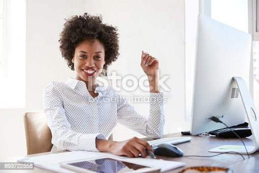 istock Young black woman in an office smiling to camera, close up 693722558