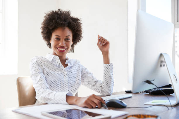 Young black woman in an office smiling to camera, close up stock photo
