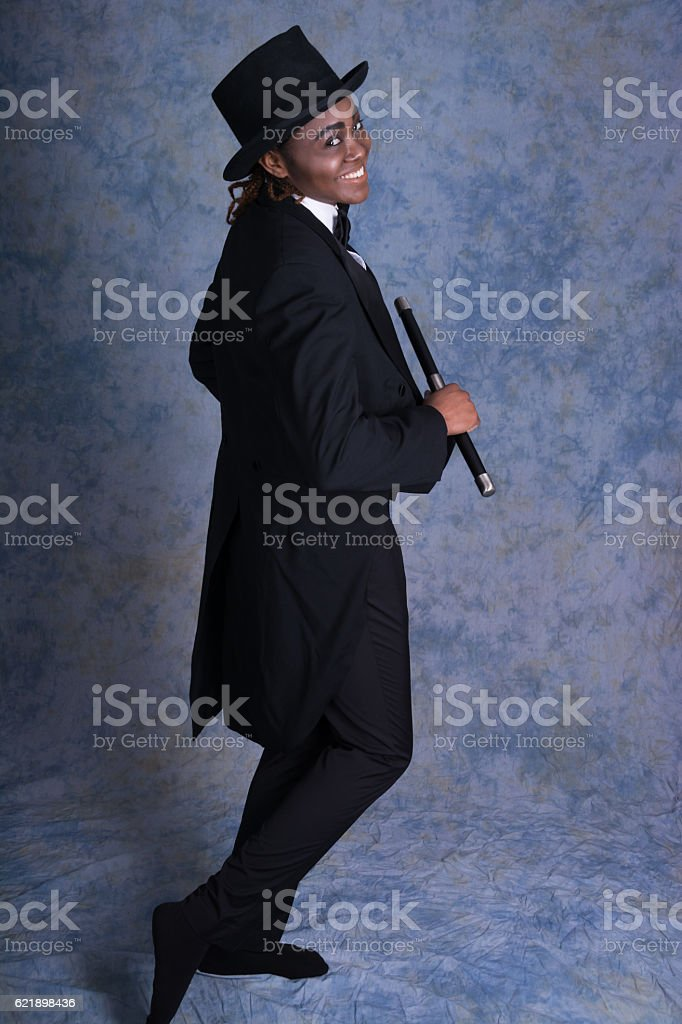 Young black woman in male drag, colour full length, studio. stock photo
