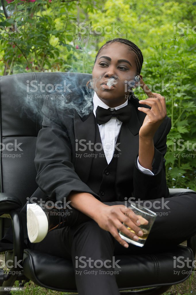 Young black woman in male drag, serious,smoking a cigar. stock photo