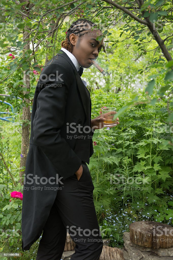 Young black woman in male drag, side view standing outdoors. stock photo