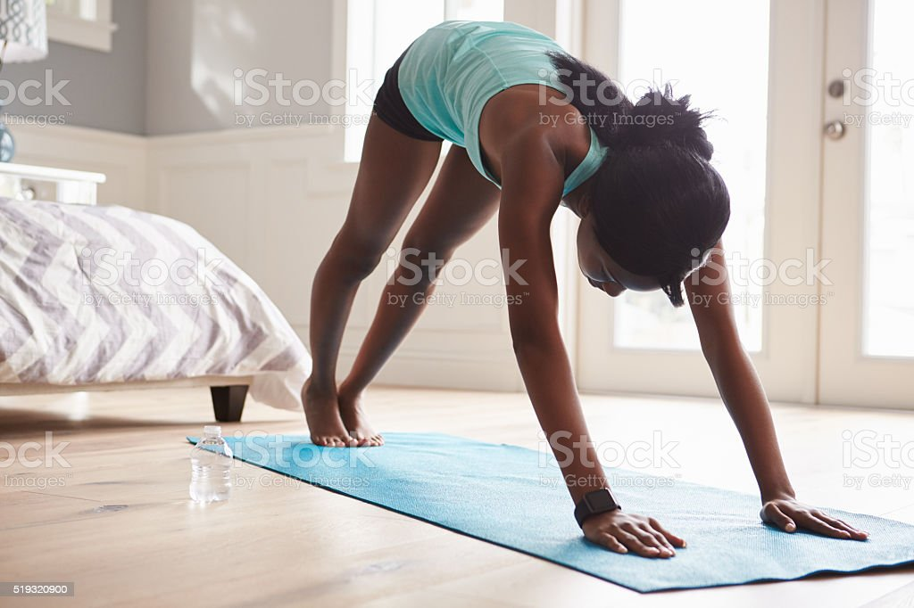 Young black woman in the downward-facing dog yoga pose stock photo