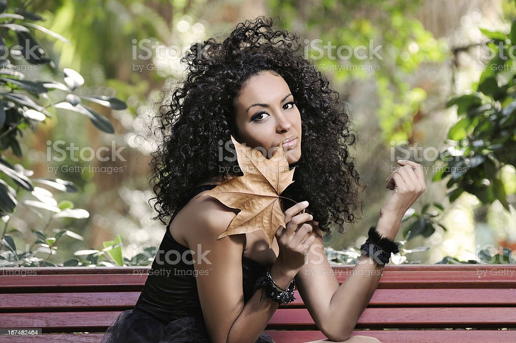 Young black woman in the park with a dry leaf royalty-free stock photo
