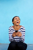 istock young black woman laughing with cell phone against blue wall 857924452