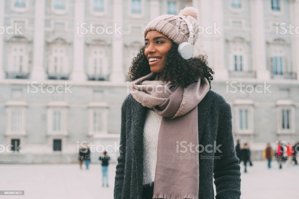 Young black woman listening to music and dancing on the mobile phone near the royal palace in winter  'n stock photo