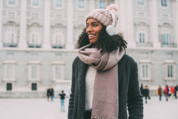 """junge schwarze frau anhören von musik und tanz auf dem handy neben dem königlichen palast im winter """"n - weihnachtsstadt stock-fotos und bilder"""
