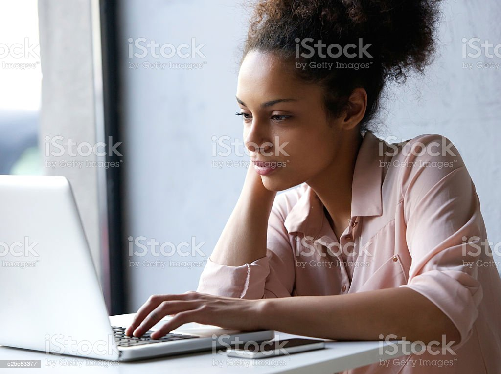 Young black woman looking at laptop stock photo
