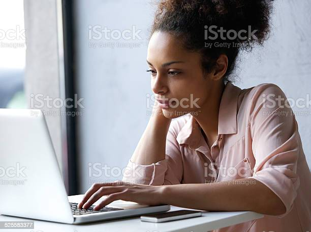 Young Black Woman Looking At Laptop Stock Photo - Download Image Now