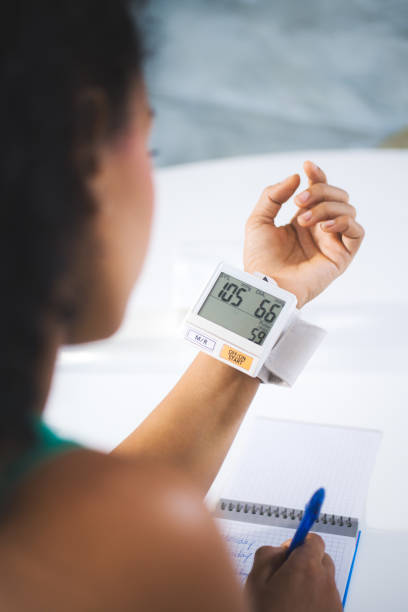 Young Black Woman Measuring Blood Pressure At Home stock photo