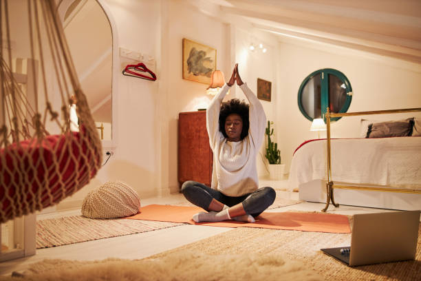 Young black woman meditating while doing yoga in bedroom stock photo