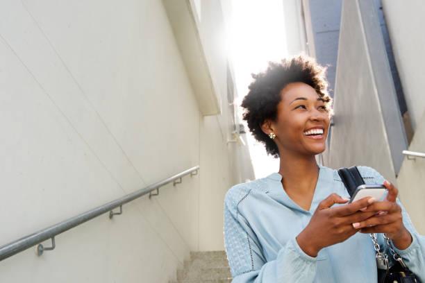 young black woman on steps with mobile phone - doğal poz stok fotoğraflar ve resimler