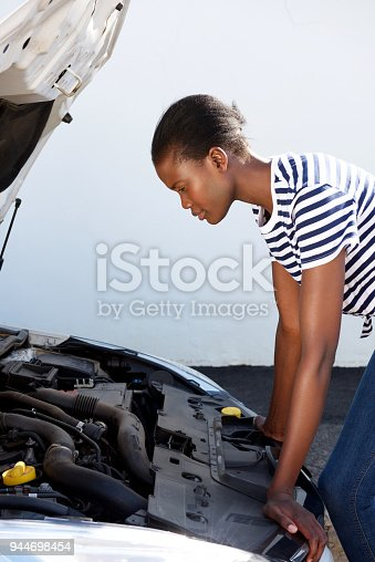 860373412 istock photo young black woman on the road trying to fix the broken down car 944698454