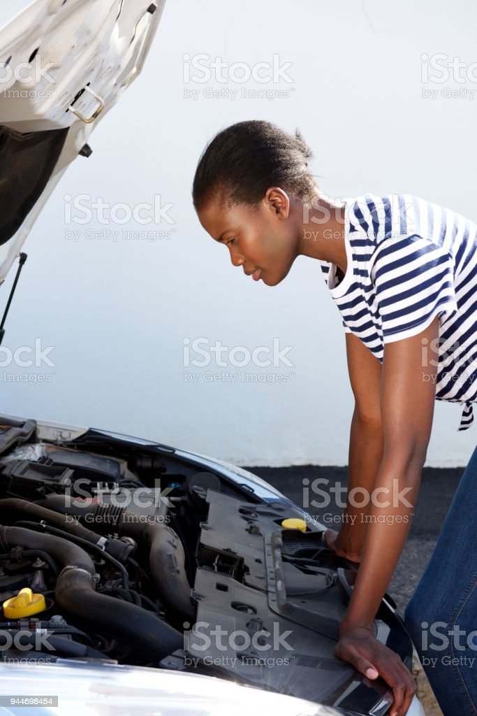young black woman on the road trying to fix the broken down car stock photo