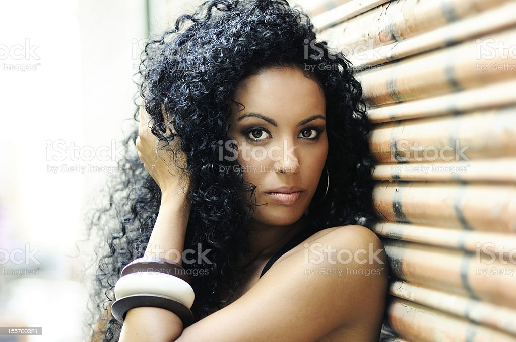 Young black woman posing against a wall stock photo
