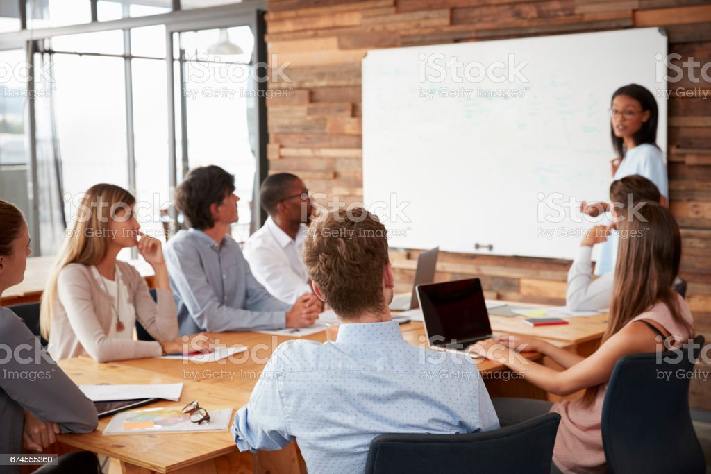 Young black woman presenting to colleagues from whiteboard stock photo