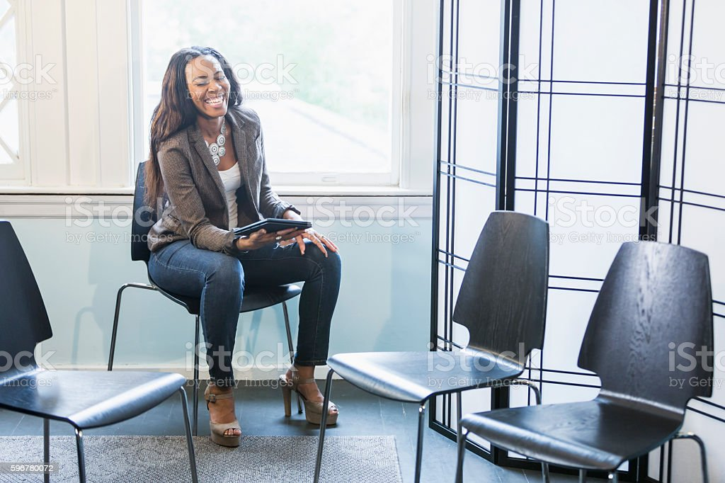 Young black woman sitting by empty chairs, laughing стоковое фото