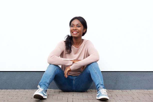 young black woman sitting on floor by white wall and smiling - sitting on floor stock photos and pictures