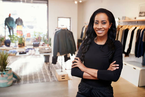 young black woman smiling to camera in a clothes shop - assistant stock pictures, royalty-free photos & images