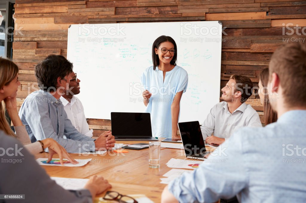 Young black woman stands addressing colleagues at a meeting - Royalty-free 20-29 Years Stock Photo