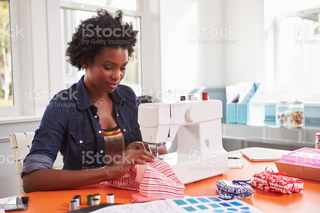 Young black woman stitching fabric using a sewing machine stock photo