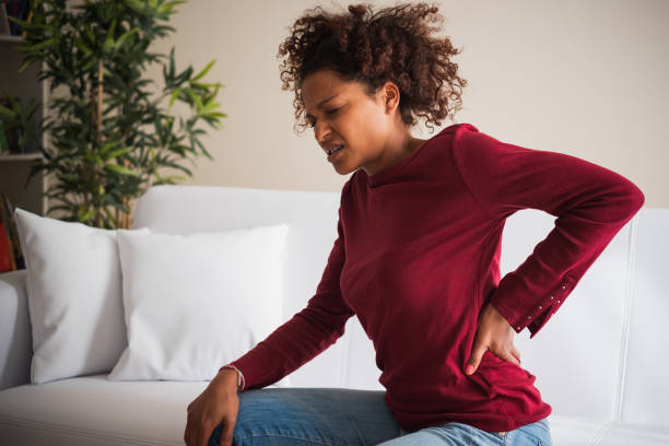 Young black woman suffer back pain cramp Back Neck pain. Painful woman holds with hand her lower back back pain stock pictures, royalty-free photos & images