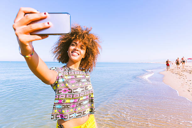 Young black woman taking a selfie at beach - Photo