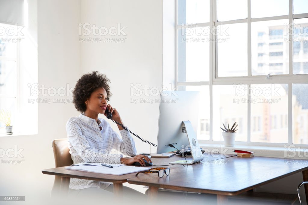 Young black woman talking on phone at her desk in an office stock photo