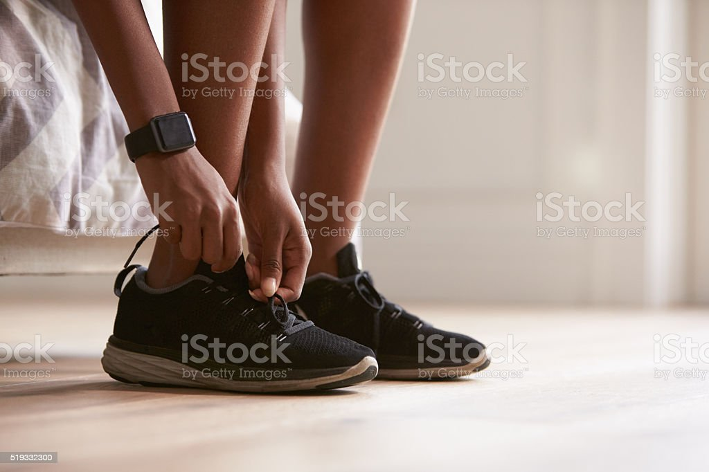 Young black woman tying sports shoes, close-up stock photo